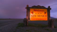 A roadside sign welcomes visitors to New Mexico as a motorhome passes. Stock Footage