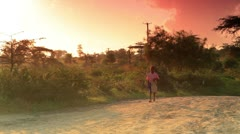 Small boy walking along a dirt road at sunrise in Africa. Stock Footage