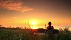 Woman sitting on a bench looking out to sea at sunset in Copenhagen, Denmark. Stock Footage