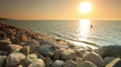 Swimming at a rocky beach at sunset in Copenhagen, Denmark. Stock Footage