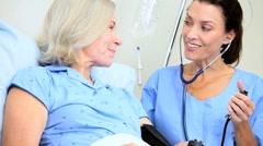 Hospital Staff Treating Senior Female Patient Stock Footage