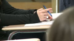 Student holding pencil getting ready to write in notebook. Stock Footage
