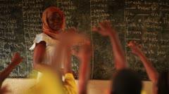 Stock Video Footage of Schoolteacher in a full classroom in Kenya.