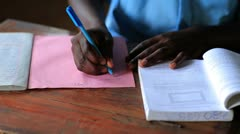Close up of hands of a school boy doing homework in Kenya. Stock Footage