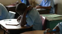 Students taking a test in a schoolroom in Kenya. - stock footage