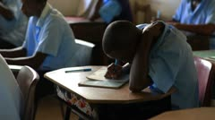 Students taking a test in a schoolroom in Africa. - stock footage