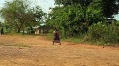 Girl carrying a little baby in a village in Kenya. Stock Footage
