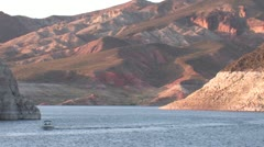 Non-descript boat on Lake Mead at sunset with mountains Stock Footage