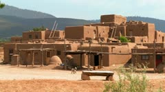 Stray dogs wander around the adobe Taos pueblo. Stock Footage