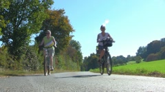 Two women on bikes passing by 02 Stock Footage