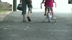 Mother walking along side child on bike with training wheels Stock Footage