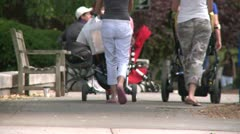 Two women with strollers walking by bench on sidewalk Stock Footage