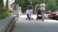 Two mothers pushing strollers down sidewalk Stock Footage