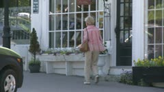 Woman walking in front of store with paned windows and window boxes Stock Footage