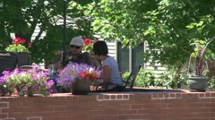 People eating at a sidewalk cafe with brick wall and potted flowers Stock Footage