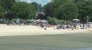 Stock Video Footage of People on the beach with umbrellas.