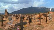 Stock Video Footage of Christian graves and crosses in the Taos pueblo cemetery.