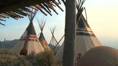 Indian teepees stand in a native american encampment. - stock footage
