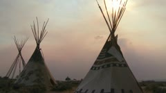 Indian teepees stand in a native american encampment at sunset. - stock footage