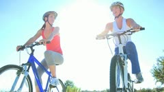 Caucasian Female Friends Cycling on Suburban Roads Stock Footage