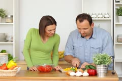 Young happy couple preparing salad at kitchen Stock Footage