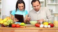 Stock Video Footage of Couple using a tablet computer during cooking