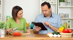 Couple using a tablet computer during cooking - stock footage