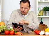 Man in kitchen with electronic tablet eat breakfast Stock Footage