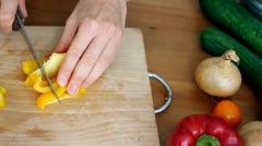 Female hands slicing yellow pepper, top view Stock Footage