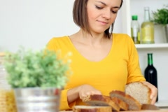 Woman slicing bread in the kitchen, steadicam shot Stock Footage