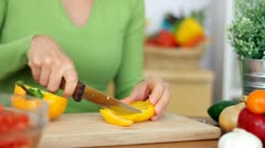 Woman slicing yellow pepper, close up Stock Footage