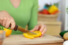 Stock Video Footage of Woman slicing yellow pepper, close up