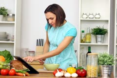 Woman using a tablet computer to cook in her kitchen - stock footage