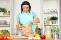 Young woman unpacking shopping bag with grocery in kitchen Stock Footage
