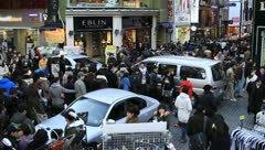 Large crowd and cars stuck on downtown street Stock Footage