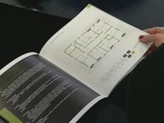 Woman choosing an apartment from booklets with apartment layout - stock footage