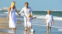 Happy Family Chasing a Ball on a Beach - stock footage