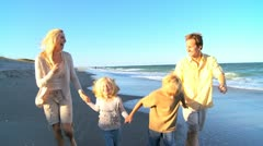 Young Caucasian Family Skipping on Beach - stock footage