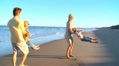 Caucasian Parents Swinging their Children on Beach Stock Footage