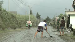 Men Scrape Thick Volcanic Ash Off Road In Indonesia Stock Footage