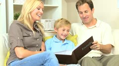 Young Family Looking Through Photo Album Stock Footage