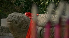 Stone turtle totem with Red ribbon,Burning incense in Incense burner,Wind of sm Stock Footage