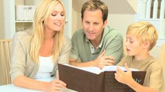 Young Boy and Parents Looking Through Family Photos - stock footage