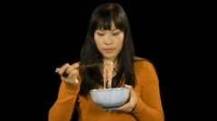 Asian female eating noodles Stock Footage