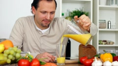 Young happy man drinking fresh healthy juice in the kitchen HD Stock Footage