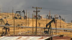 Oil & gas, hillside field of pump-jacks Stock Footage