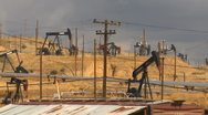Stock Video Footage of oil & gas, hillside field of pump-jacks