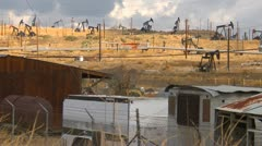Oil & gas, field of pump-jacks with old abandoned trailers Stock Footage
