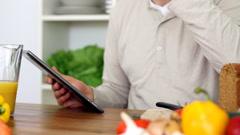 Man using digital tablet and drinking orange juice HD Stock Footage