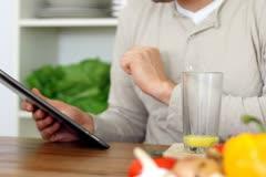 Man using digital tablet and drinking orange juice NTSC Stock Footage